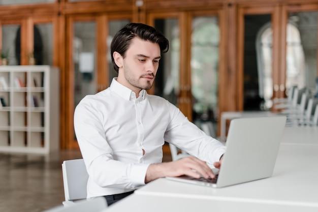 Man op zijn werkplek met laptop op kantoor