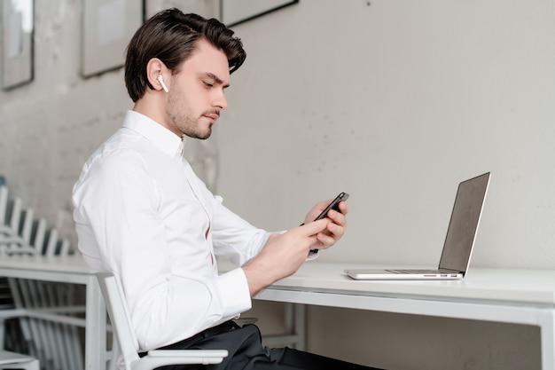 Man op zijn werkplek met telefoon en laptop op kantoor