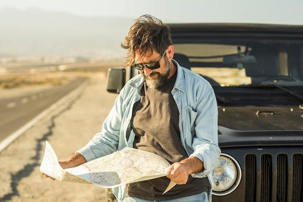 Man op zoek naar kaart leunend op voertuig langs de weg. volwassen man die de locatie van de bestemming controleert op een papieren kaart die buiten de auto staat. man zoekt navigatieroute met papieren kaart langs de weg