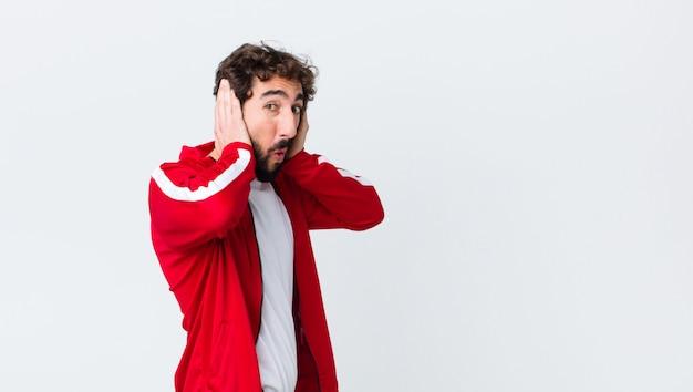 Man op zoek onaangenaam geschokt, bang of bezorgd, mond wijd open en beide oren bedekkend met handen