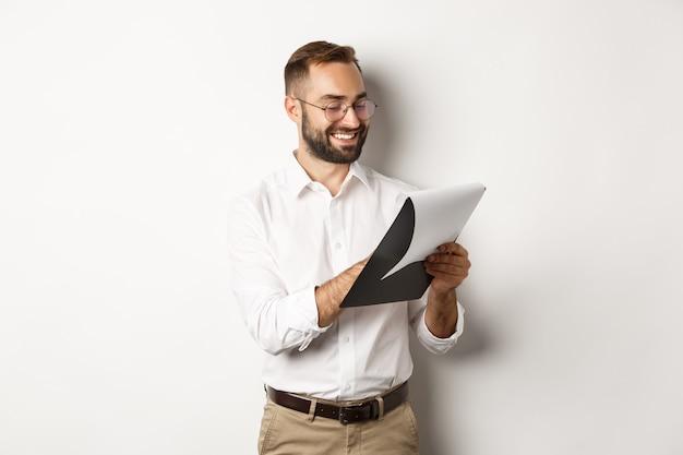 Man op zoek tevreden tijdens het lezen van documenten, klembord vasthouden en glimlachen, staan
