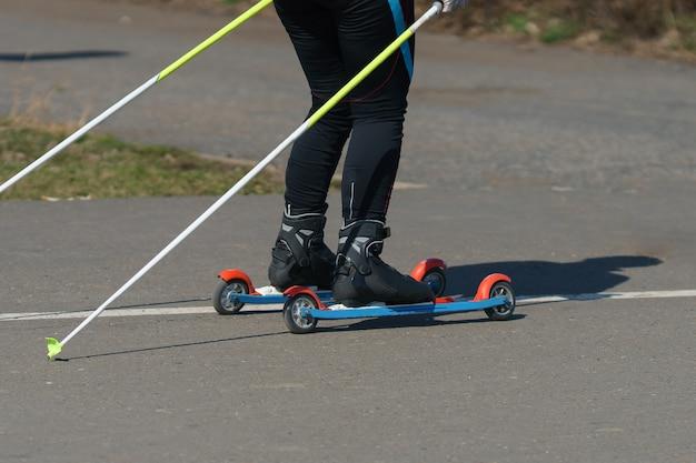Man op zomer ski's rijdt op een asfaltweg.