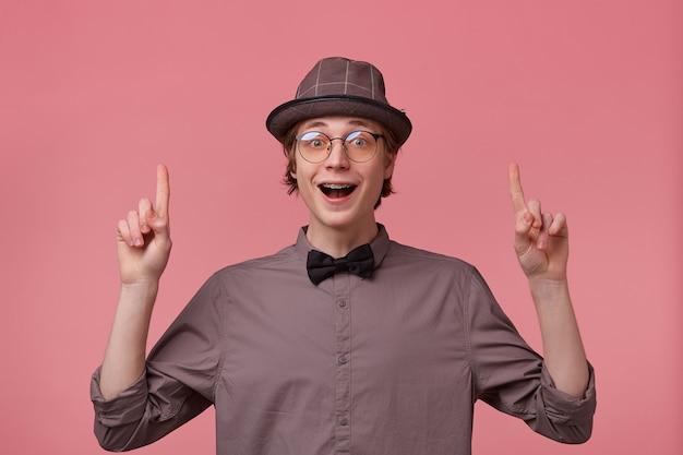 Man opende zijn mond van opwinding, is overweldigd door positieve emoties geluk vreugde wijzend wijsvinger omhoog trekt de aandacht, gekleed in hemd hoed vlinderdas bril heeft beugels geïsoleerd op roze