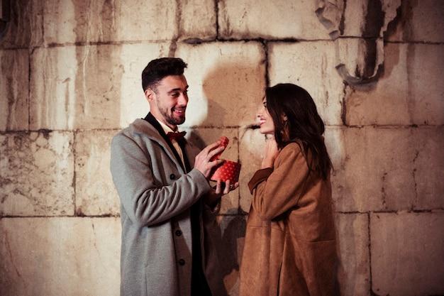Man opening geschenkdoos om mooie vrouw in straat
