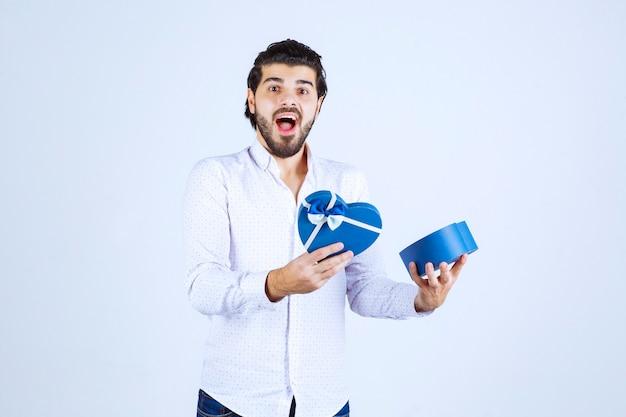 Man opent een blauwe geschenkdoos en wordt verrast
