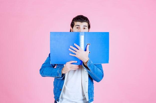 Man opent een blauwe map en verbergt zijn gezicht erachter
