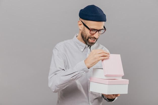 Man opent geschenkdoos, kijkt nieuwsgierig, draagt een bril, hoed en wit shirt, staat tegen een grijze achtergrond