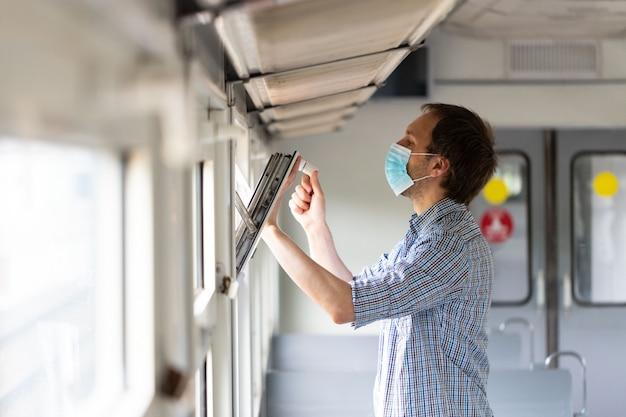 Man opent raam in trein om frisse lucht en ventilatie in te ademen en draagt beschermend masker tijdens nieuwe normale verandering na covid-19-uitbraak