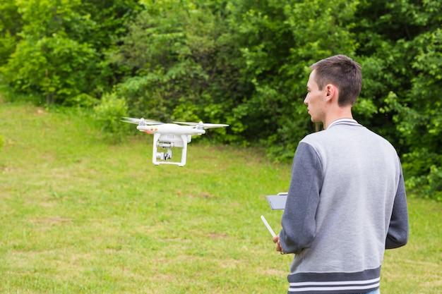 Man operationele drone vliegen of zweven door afstandsbediening in de natuur