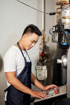 Man operationele koffiebranderij machine