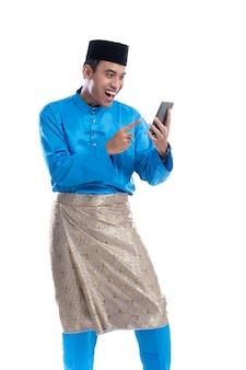 Man opgewonden tijdens het kijken naar zijn telefoon op witte achtergrond