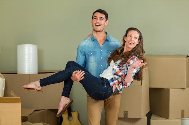 Man opheffing vrouw in zijn armen in hun nieuwe huis