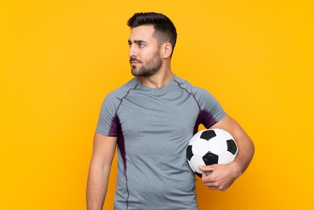 Man over geïsoleerde gele muur met voetbal