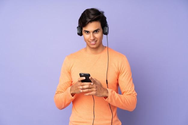 Man over paarse muur luisteren muziek met een mobiele telefoon