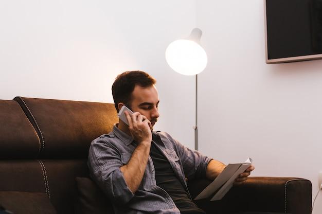 Man papier houden en praten over de mobiele telefoon zittend op de bank thuis