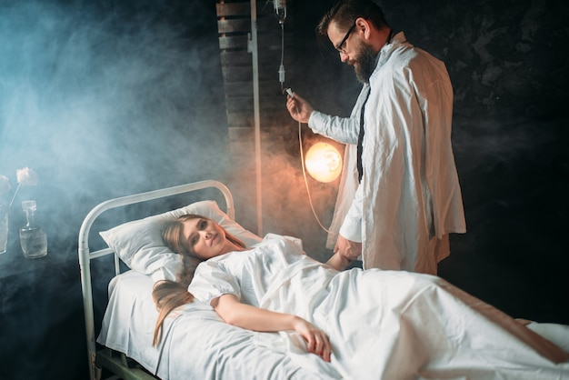 Man past het infuus van zieke vrouw in het ziekenhuis aan