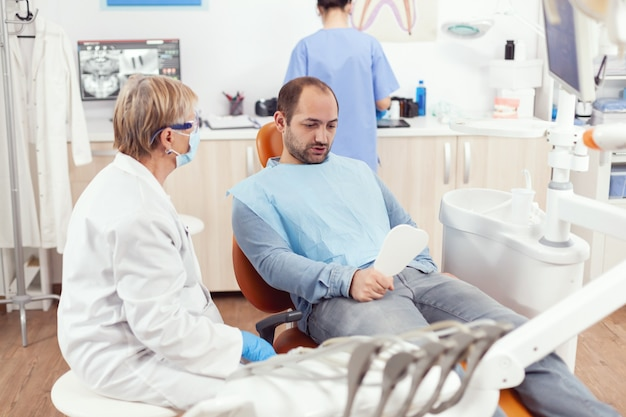 Man patiënt in spiegel kijken na medisch stomatologisch team dat tandheelkundige chirurgie afrondt tijdens stomatologieprocedure