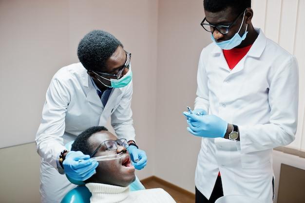 Man patiënt in tandartsstoel. tandartsbureau en het concept van de artsenpraktijk. professionele tandarts die zijn patiënt helpen bij medische tandheelkunde. injectie-verdoving.
