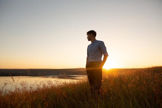Man permanent en genieten van de prachtige zonsondergang over een brede riviervallei.