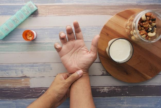 Man pijn in de hand lijden met medische pillen melk en amandelnoot op tafel