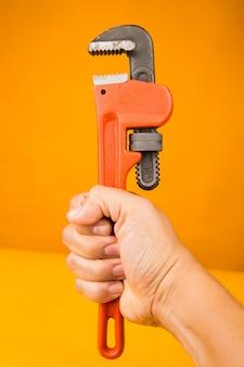 Man pijp moersleutel in de hand houden
