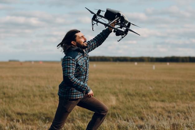 Man piloot met quadcopter drone in de hand en rennen op buitenveld