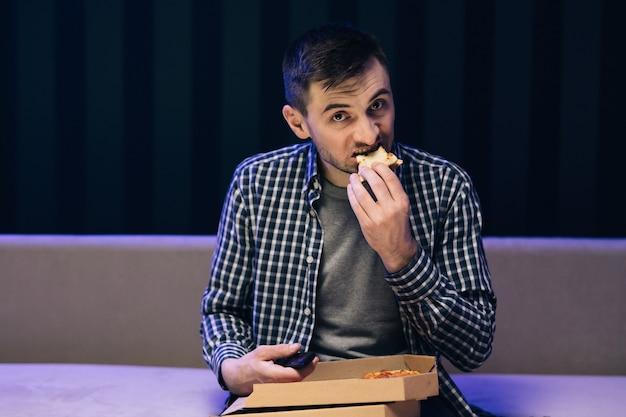 Man pizza eten tijdens het kijken naar tv