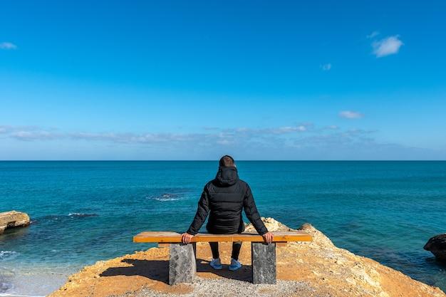 Man plaatsing aan de kust, kijkend naar de kalme zee.