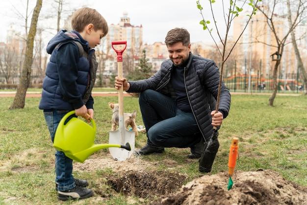 Man plating in de grond een kleine boom