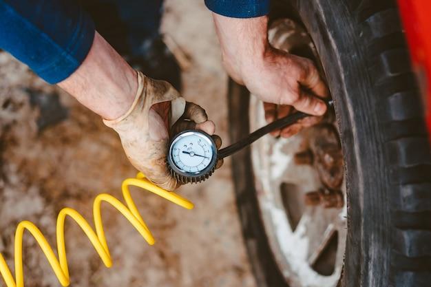 Man pompt luchtwiel met een compressor