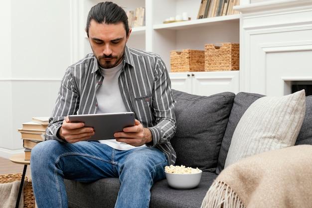Man popcorn eten en met behulp van een digitale tablet