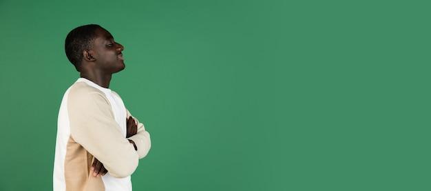 Man portret geïsoleerd op groene studiomuur