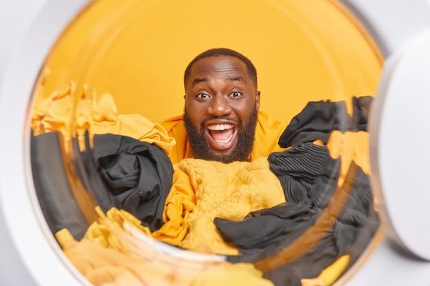Man poseert door wasmachine trommel heeft een vrolijke uitdrukking laat witte tanden zien doet thuis de was doet de wasmachine