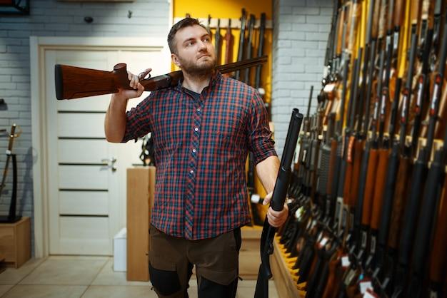 Man poseert met twee geweren bij vitrine in wapenwinkel