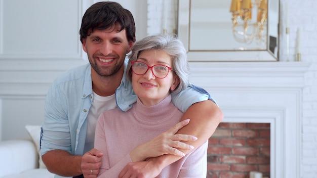 Man poseert met zijn moeder bij haar thuis.