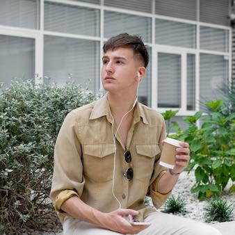Man poseren buitenshuis terwijl koffie drinken en luisteren naar muziek op oortelefoons