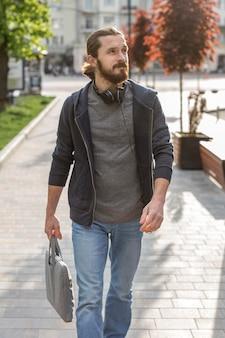 Man poseren in de stad terwijl het dragen van een koptelefoon