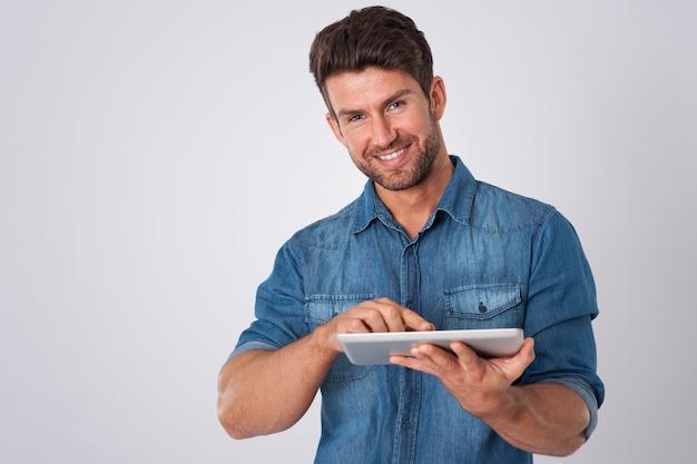 Man poseren met denim overhemd en tablet