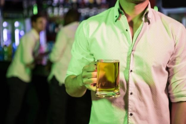 Man poseren met glas bier en vrienden op ba