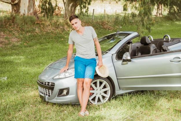 Man poseren voor zijn auto