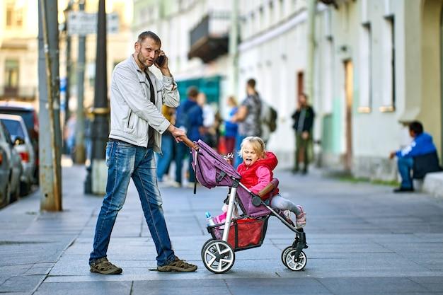 Man praat via smartphone terwijl hij wandelt met klein meisje in kinderwagen