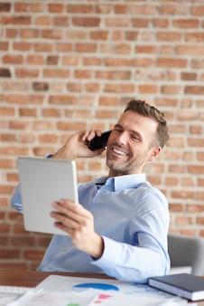 Man praten aan de telefoon en bladeren door digitale tablet