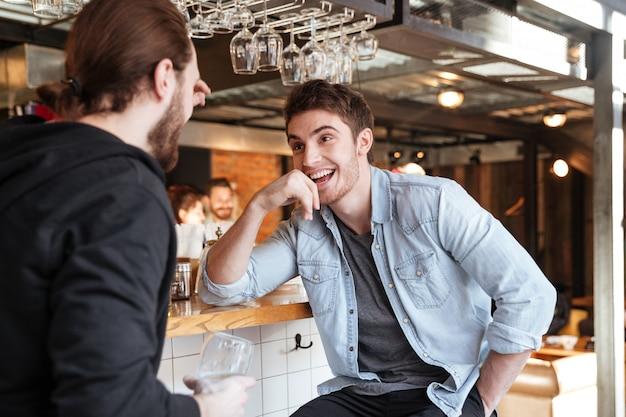 Man praten met zijn vriend in de bar