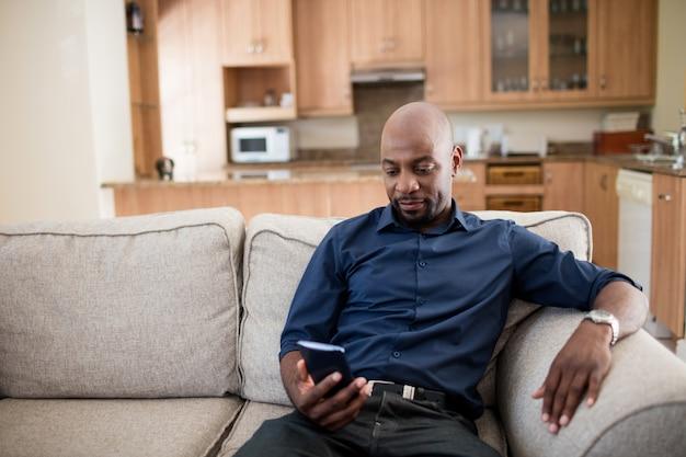 Man praten op mobiele telefoon in de woonkamer