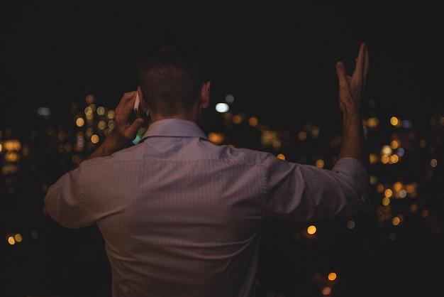 Man praten op mobiele telefoon 's nachts
