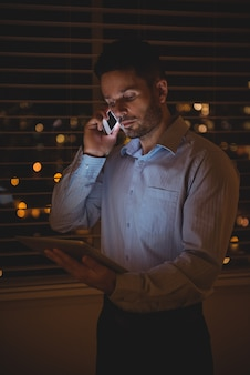 Man praten op mobiele telefoon tijdens het gebruik van digitale tablet