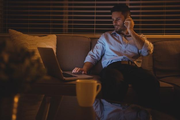 Man praten op mobiele telefoon tijdens het gebruik van laptop in de woonkamer