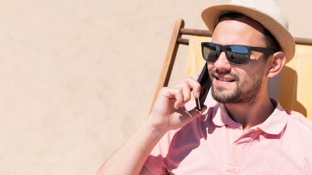 Man praten over smartphone in strandstoel