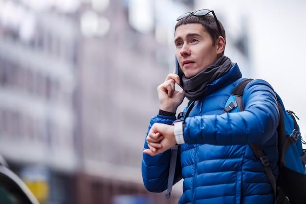Man praten over telefoon en kijken naar smartwatch