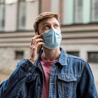 Man praten over zijn telefoon terwijl hij buiten een medisch masker draagt